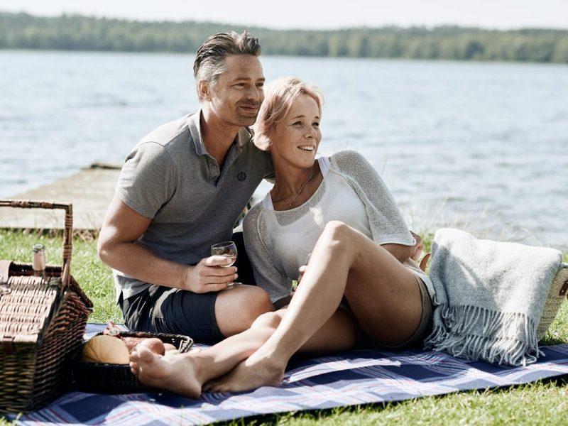 Par sidder udendørs med picknick kurv